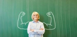 Alte starke Frau als Lehrer vor Tafel mit Muskeln in der Schule