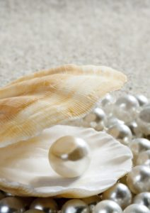Caribbean pearl inside clam shell over white sand beach